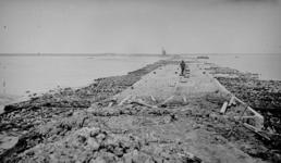 336 - 'Levensstrijd'. Man loopt over houten planken over de caissons op dijk in aanbouw