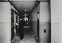191771 Interieur van het hoofdbureau van de politie: cellengang. Links agent Van Alphen. Op de achtergrond ...