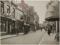 69347 De Vrijstraat met linksvoor kapperszaak L. Reemers en fruit- en groentenwinkel H. van Rijt, op nr. 13 en 15, ca. 1935