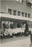 192937 Het aanbieden van textielproducten. Op de achtergrond het pand van de Amsterdamsche Bank, ca. 1930