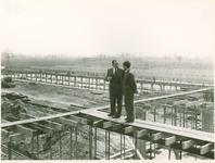 135100 Weth Braam met de aannemer boven op de steiger bij het in aanbouw zijnde nieuwe beton fabriek te Son, 26-04-1956