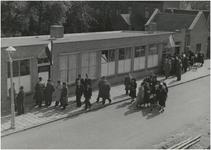 196533 Het bezichtigen van de winkels, met rechts bovenin rund- en varkensslagerij, 05-1948