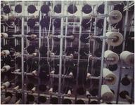 116668 Textielfabriek Diddens en Van Asten. Klossenrek achter één van de breimachines, 1982