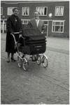 47635 Leun en Zus Schepens met kinderwagen (Hans Teeuwen) op de Markt in Budel. Op achtergrond bakkerij Rooijmans, 1967