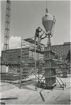 718 Bouwwerkzaamheden: het gieten van beton in een bekisting. Met op de achtergrond verzorgingshuis de Ravenshof en het ...