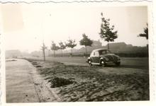 577723 Volkswagen kever op de Dijkstraat. Het hoge pand in het midden, op de achtergrond, is de huishoudschool, 1959