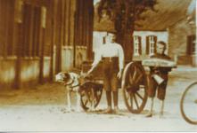 576016 Hondenkar met twee jongens ernaast op de Markt; Één jongen draagt een schenkkan en mogelijk een brood, 1910