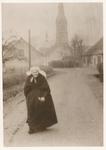 576480 Mevrouw Berkvens loopt op de Jan van Havenstraat en komt uit de kerk, 1935-1940