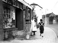 ehc_gp_116 Passerende huisvrouw groet 2 winkelvrouwen van de kruidenierswinkel, die de ramen aan het wassen zijn 29-10-1937