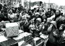 BR_SINTERKLAAS_1990_009 De intocht van Sinterklaas in Brielle. Kinderen en ouders kijken naar de wagen vol pakjes; 17 ...