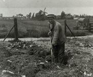 B-945XIV Een personeelslid van Gemeentereiniging met hark op de stortplaats op een weiland in de omgeving van ...