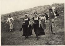 2404 Golfspelers op de golfbaan te Domburg met twee meisjes in Walcherse klederdracht, die de caddy's dragen
