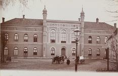 3829 Gezicht op de voorgevel van het Gasthuis aan het Noordpoortplein te Middelburg met poserende jeugd; rechts een wegwijzer
