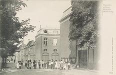 3854 Gezicht op het Hofplein te Middelburg met voor het gerechtsgebouw een groep poserende jeugd; aan de blinde muur ...