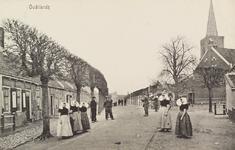 5736 Gezicht op de met leilinden beplante Dorpsstraat in Oudelande, met rechts de toren van de Nederlandse Hervormde kerk