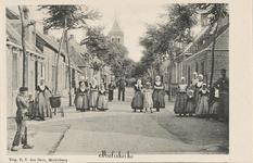 587 Gezicht op een straat te Meliskerke met poserende inwoners en op de achtergrond de Ned. Herv. kerk