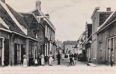 7404 Gezicht op de Oudelandsestraat in de richting van Markt en Kerkstraat in Tholen, met de slijpsteen van smidsbaas ...