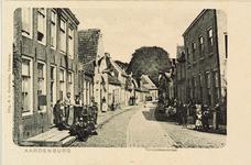 8030 Gezicht op de Tuimelsteenstraat te Aardenburg met uitgestoken vlaggen poserende personen