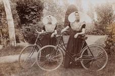 9347 Twee vrouwen in protestantse, Zuid-Bevelandse dracht poseren in een park met hun fiets