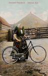 9406 Een meisje in Axelse dracht poseert met haar fiets op het erf van een boerderij