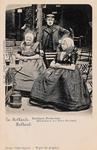 9418 Een echtpaar met hun dochter in Axelse dracht op het terras van een café. Let op het spoormandje en de paraplu