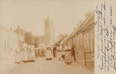 9460 Poserende personen, waaronder een aantal vrouwen in protestantse, Zuid-Bevelandse dracht, in de Dorpstraat te ...