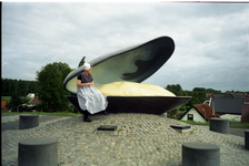 BRU-2839 Bruinisse. Havenkade. Zittend op het monument voor de mosselvisserij wordt geposeerd door iemand in de Bruse ...