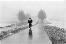 JVH-1617 Zierikzee. Lange Blokweg. Sneeuw in april. Fietser fietst in wit landschap in de richting van de overgang over ...