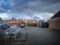 JVH-8012 Bruinisse. Dreef. Parkeerterrein met winkelwagentjes van de supermarkt van Albert Heijn. Rechts de achterkant ...