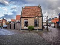 JVH-8022 Bruinisse. Poststraat. Een huisje op het kruispunt Poststraat op de voorgrond, linksboven de Kerkstraat en ...
