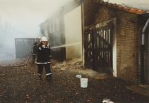 950008 Brandweer bezig met het blussen van een brand in een boerenschuur in de Dijckmeesterpolder bij Philippine