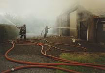 950010 Brandweer bezig met het blussen van een brand in een boerenschuur in de Dijckmeesterpolder bij Philippine