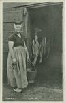 KLD-P-179 Een vrouw in Zeeuwse dracht bij een koeienstal