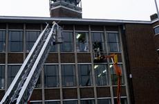 21822 De werkbak van de hoogwerker van de brandweer wordt naar haar juiste positie gedirigeerd. Deze hoogwerker was te ...