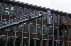 22110 De werkbak van de hoogwerker van de brandweer op de juiste plaats gebracht. De hoogwerker was te hulp geroepen om ...