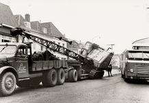 28104 Het wegdek in de Coosje Buskenstraat werd licht beschadigd toen een graafmachine van een vrachtauto afgleed.