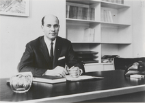 M 11292 Man poserend achter bureau