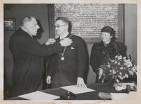 M 12095 De loco-burgemeester wethouder A.M. Ebben, hangt de nieuwe burgemeester Cambier van Nooten de ambtsketting om. ...