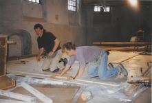 0690-3956 A. Winkel links met collega bij het maken van de vloer voor de banken in dekerk.