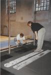 0690-3958 Tegelzetter bij het aanbrengen van de vloertegels in de kerk A. Winkel rechts kijkt toe.