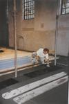 0690-3959 Tegelzetter bij het aanbrengen van de vloertegels in de kerk.
