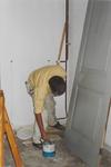 0690-3961 De schilder bij het schilderen van een deur in de kerk tijdens de restauratie.