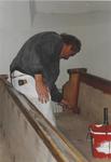 0690-3962 De schilder bij het schilderen van de kerkbanken tijdens de restauratie van de kerk.