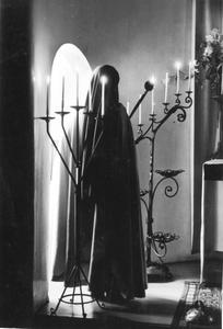 102033 Zuster steekt de kaarsen aan in de kapel