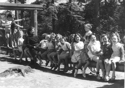102081 Zuster Marie met kinderen uit Amsterdam in de speeltuin op de familieschommel