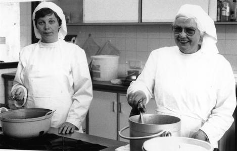 102093 Zuster Maria Leunissen en zr. Gabriëlle Emke tijdens het koken in de Stad Gods te Amsterdam