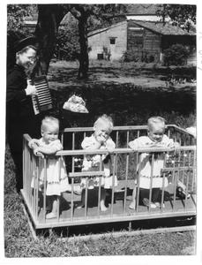 102143 Zuster Evangelista speelt accordeon voor een drieling te Valkenswaard