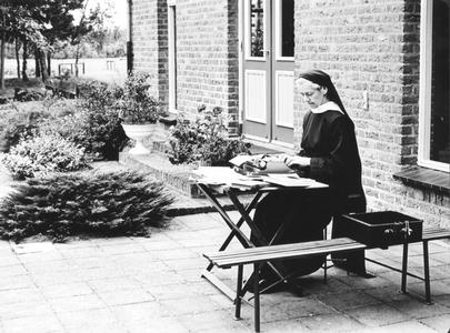 200015 Met mooi weer wordt het kantoorwerk naar buiten verplaatst in de priorij te Heesch