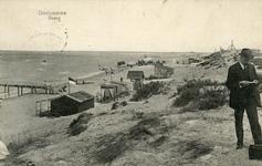 PB4963 Duin en strand met toegang tot steiger voor boot. Een man staat iets te lezen op het duin, 1912