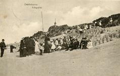 PB5276 Een groep kinderen en volwassenen zitten tegen de duinen nabij Koepel Zeeburg, ca. 1916